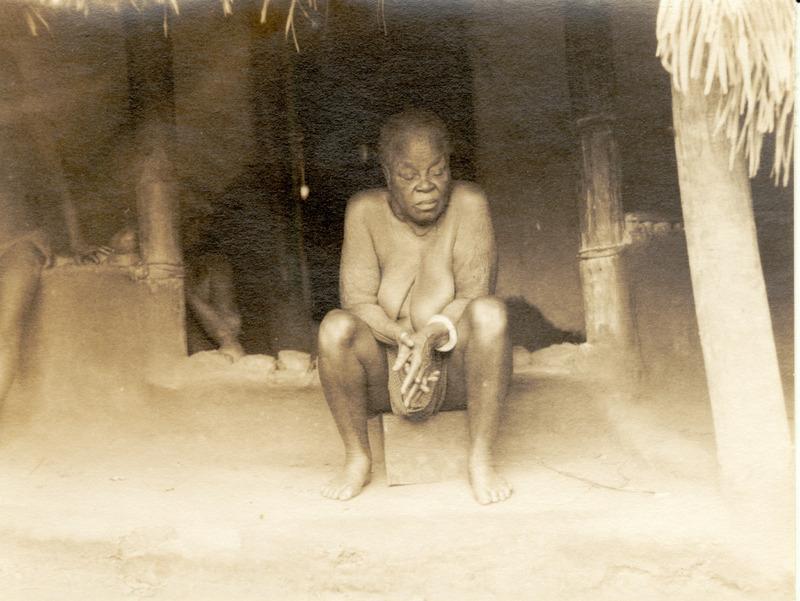 Alternate view of Chief Suah Koko sitting in house doorway, Suah Koko, Liberia